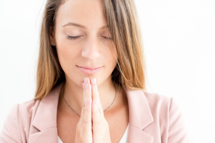 Close-up of serene young businesswoman praying
